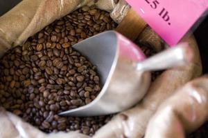 zak koffiebonen met metalen lepel foto