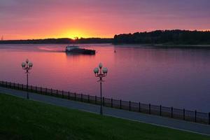 schip op de rivier bij zonsondergang foto