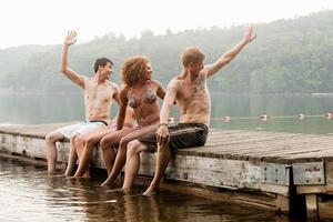 vrienden draaien om te zwaaien vanaf de pier op het meer foto