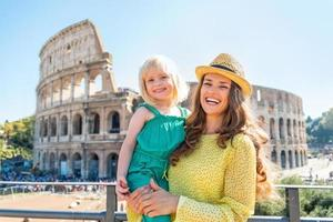 gelukkige moeder en babymeisje dichtbij colosseum in rome, italië