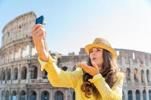 vrouwentoerist die selfie blazende kussen nemen in rome colosseum foto
