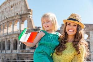 lachende moeder en dochter zwaaien Italiaanse vlag door colosseum