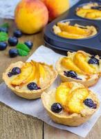 zelfgemaakte taartjes met perzik en bosbessen foto