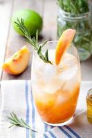 perzik en rozemarijn bruisen cocktail op een houten achtergrond. cocktail.