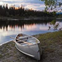 zonsonderganghemel en kano bij teslinrivier yukon Canada foto