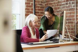 twee vrouwelijke ondernemers bijeen in creatieve kantoor foto