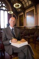 hogere mannelijke registrar die document, portret voorbereidingen treft te ondertekenen foto