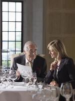zakenman en vrouw het lezen van documenten aan restaurant tafel foto