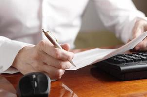 handen met document en pen op een computertoetsenbord foto
