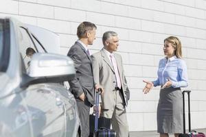 zakenlui die met bagage buiten auto bespreken