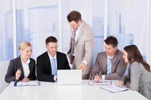 mensen uit het bedrijfsleven bespreken op laptop in kantoor foto