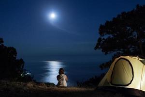 silhouet van vrouw in de buurt van tent 's nachts