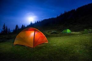 twee verlichte oranje en groene kampeertenten foto