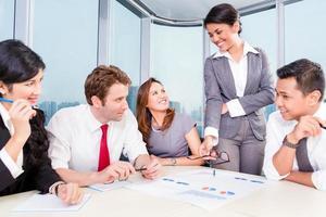 Aziatische business team bespreken grafieken foto