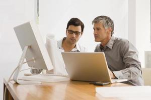 twee zakenlieden die een blauwdruk in een bureau bespreken