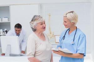 verpleegster bespreken met patiënt terwijl arts computer gebruikt foto