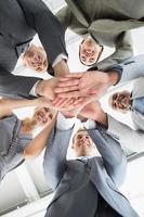 medewerkers handen in elkaar steken foto