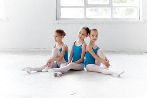 drie kleine balletmeisjes zitten en poseren samen foto