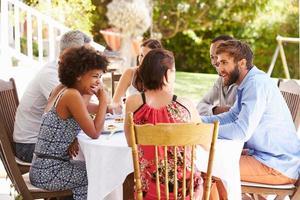 vrienden samen dineren aan een tafel in een tuin foto