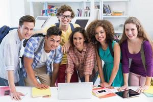 gelukkige studenten werken samen aan laptop foto