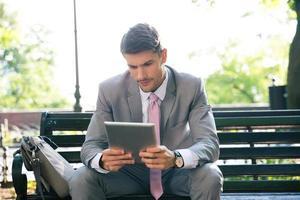 zakenman die tabletcomputer in openlucht met behulp van foto