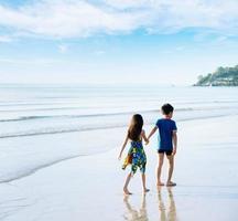 broer zus hand in hand lopen op het strand foto