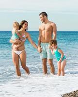 gezin van vier op het strand foto