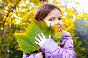 kind een piek behing gevallen herfstbladeren foto