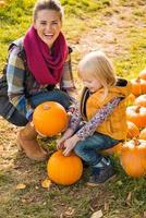 glimlachende moeder en kind die pompoenen kiezen foto