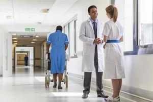 artsen ziekenhuis gang verpleegster duwen rolstoel foto