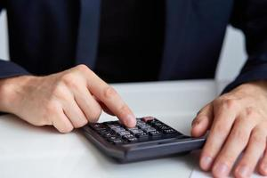 mannen handen met rekenmachine foto