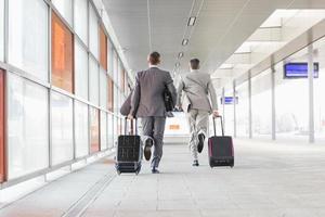 zakenlieden met bagage die op spoorwegplatform lopen
