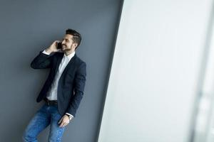 jonge man met mobiele telefoon in het kantoor foto