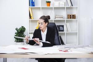 vrouwelijke architect die plannen bestudeert foto