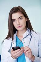 jonge vrouwelijke arts sms'en foto