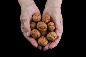 oude vrouwelijke handen met walnoten foto