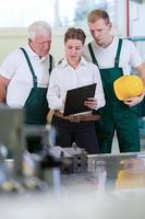vrouwelijke ingenieur en fabrieksarbeiders foto