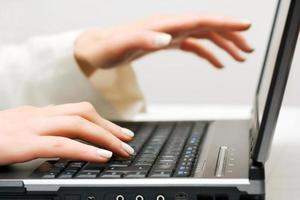 vrouwelijke handen die op laptop werkt