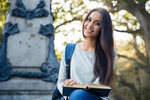 lachende vrouwelijke student met boek foto