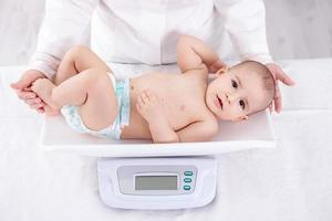 vrouwelijke kinderarts met een gewicht van baby in kantoor foto