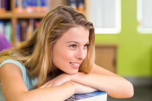 doordachte mooie vrouwelijke student in bibliotheek foto