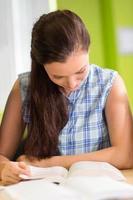 vrouwelijke student leesboek in bibliotheek foto