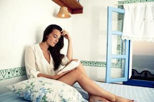 jonge vrouwelijke leesboek op bed foto