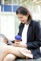 jonge vrouwelijke Aziatische zakenman met behulp van tablet