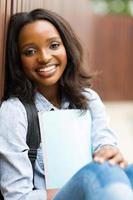 vrouwelijke Afrikaanse student buiten zitten foto