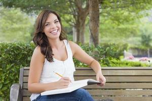 jonge volwassen vrouwelijke student op bankje buitenshuis foto