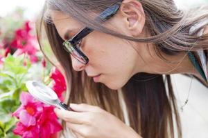 jonge vrouwelijke tuinman bewaakt de gezondheid van bloemen foto