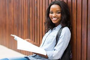 vrouwelijke Afrikaanse student die een boek leest foto