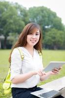 Aziatische vrouwelijke student die tablet in campus gebruiken foto