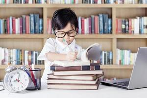mooie vrouwelijke student schrijven in de bibliotheek foto